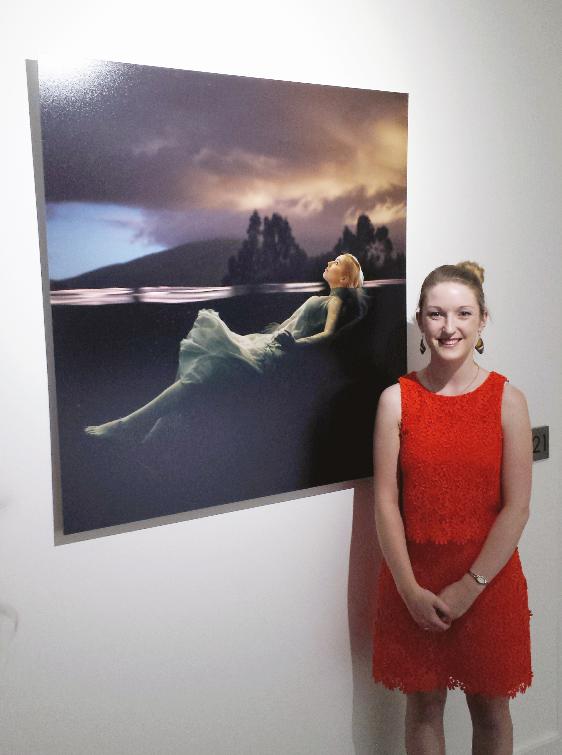 Julia Nance with her printed fine art portrait 'Swan' on permanent exhibition at the 2 Girls Building in Abbotsford.