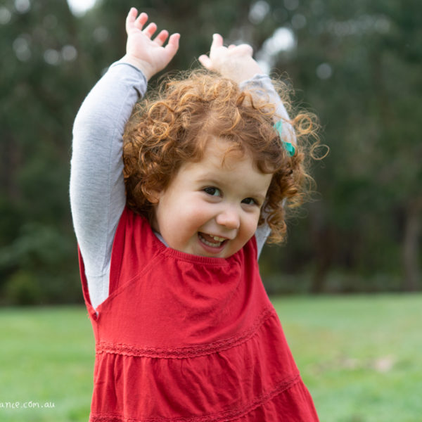Young girl explores outside for family portraits at Melbourne family portrait studio