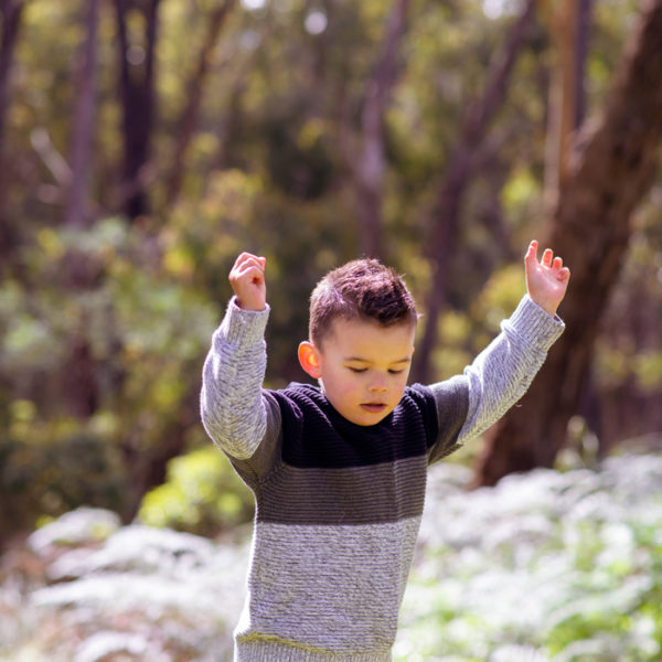 Boy explores bushland with hands in air at Melbourne family portrait studio