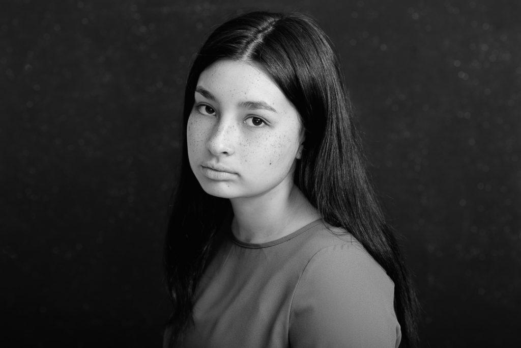 Serious fine art portrait in black and white of teenage girl in Melbourne family portrait studio.