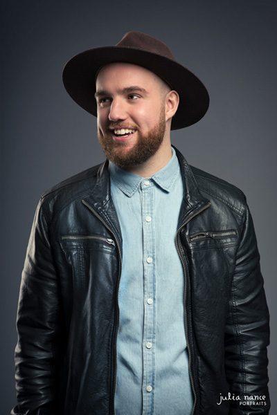 Smiling man wears a hat in Melbourne portrait studio.