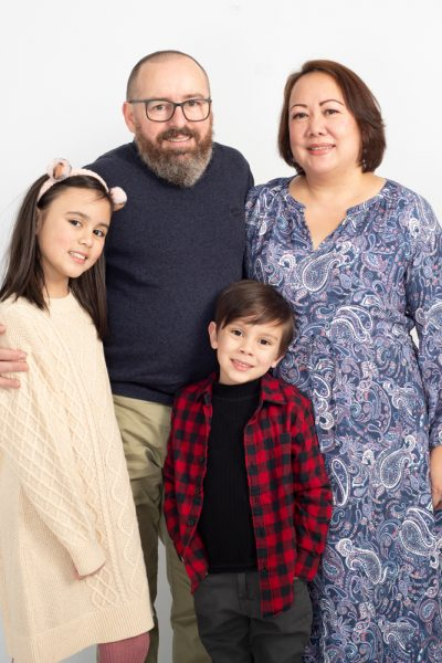 Studio family portrait photograph of family of four on a white background
