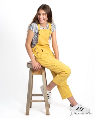 Girl in yellow overalls laughs away from the camera at a Melbourne family portrait studio